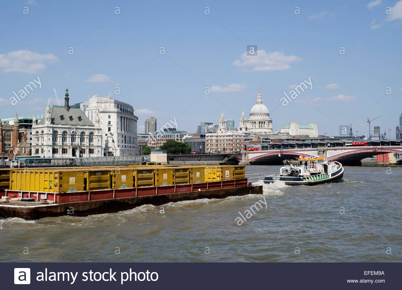 Tug pulling a loaded cargo lighter on the River Thames, approaching Blackfriars Bridge, and with St Pauls Cathedral - Stock Image