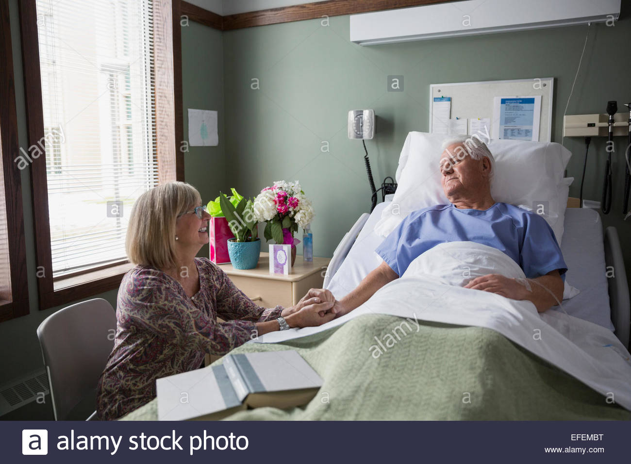 Wife holding husbands hand in hospital room - Stock Image