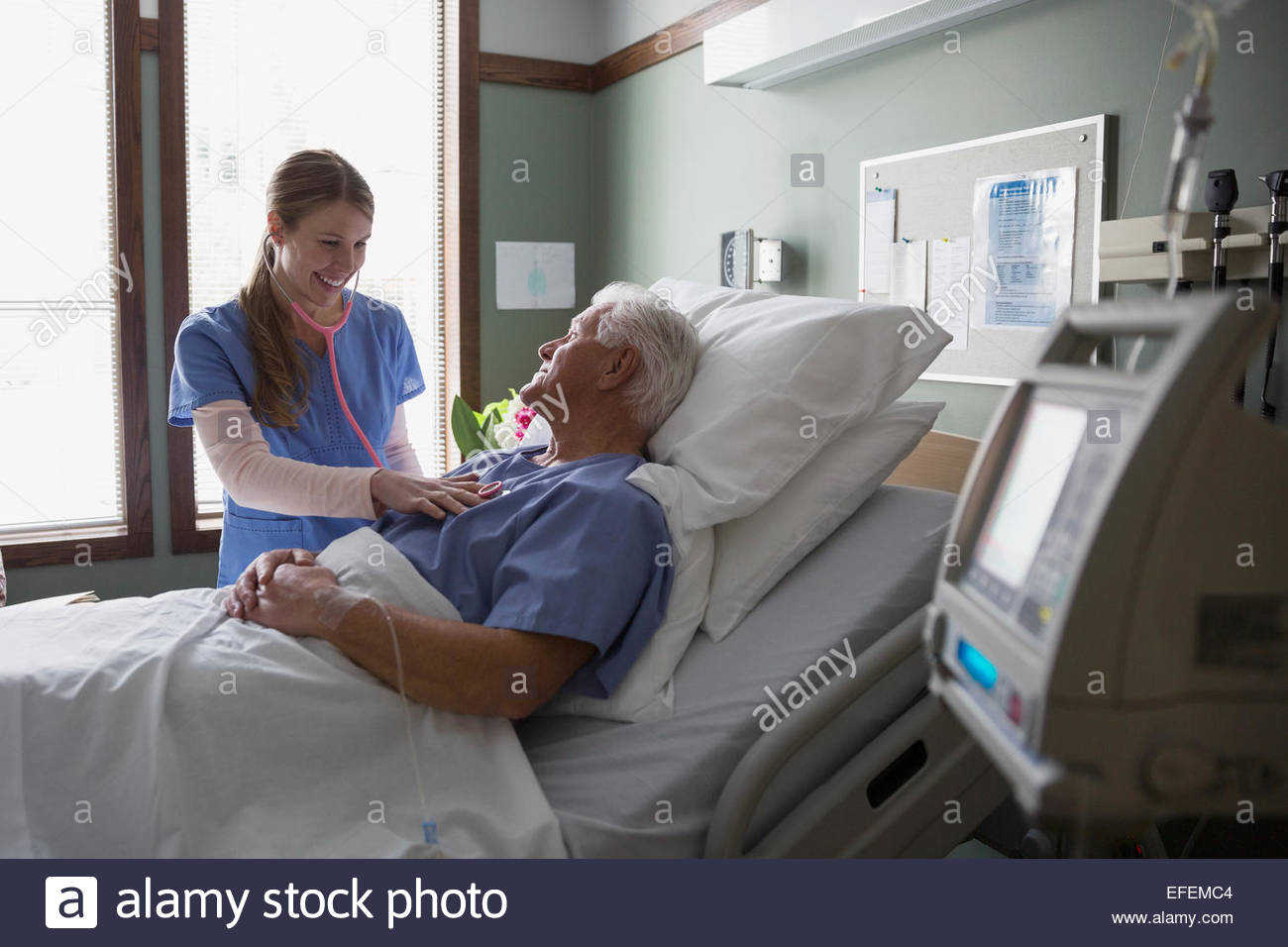Nurse using stethoscope on patient in hospital room - Stock Image