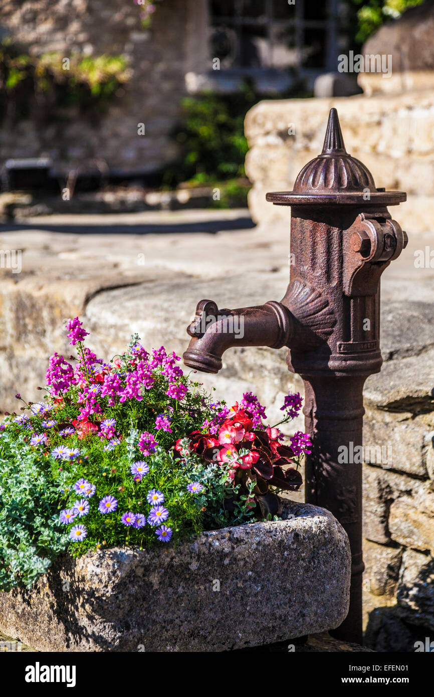The old village pump in the Cotswold village of Castle Combe  in Wiltshire. - Stock Image