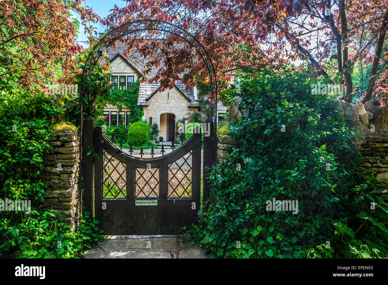 View through the garden gate of a country house in the Cotswolds in Wiltshire. - Stock Image