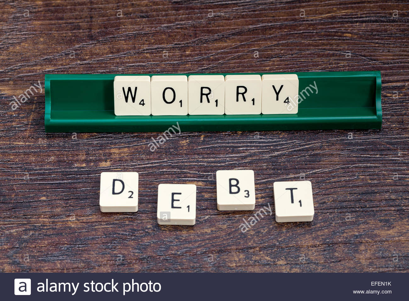 Worry and Debt spelled out with scrabble letters - Stock Image