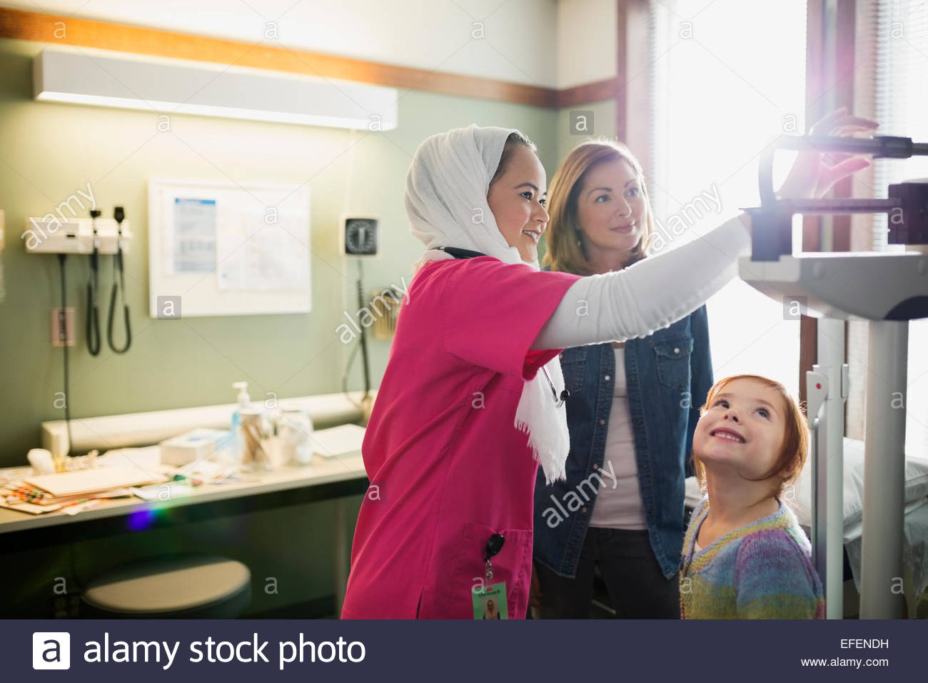 Nurse checking weight of girl in examination room - Stock Image