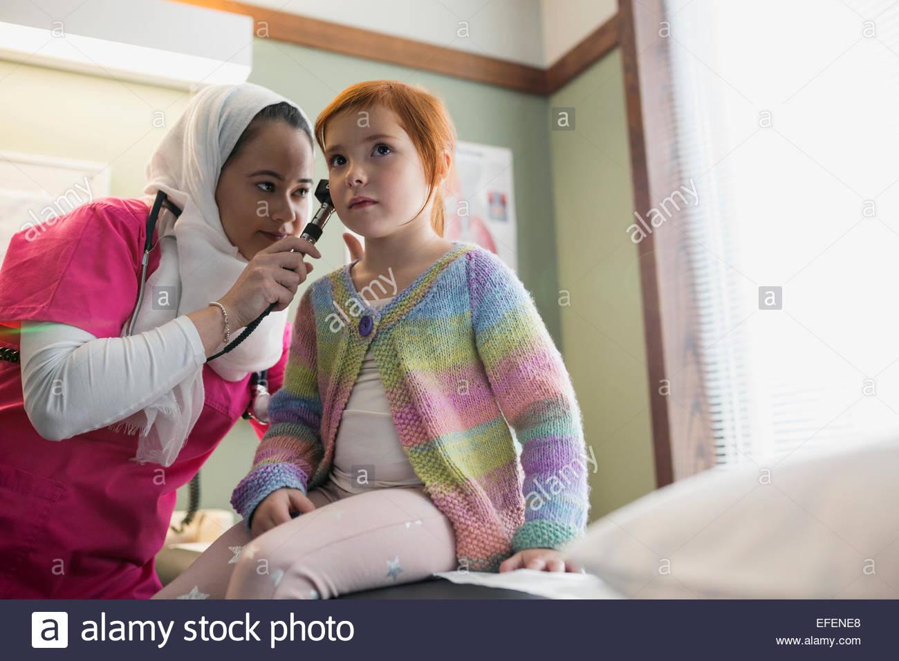 Nurse wearing hijab checking ears of girl - Stock Image
