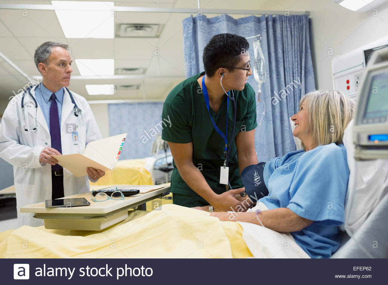 Male nurse checking patients blood pressure in hospital - Stock Image