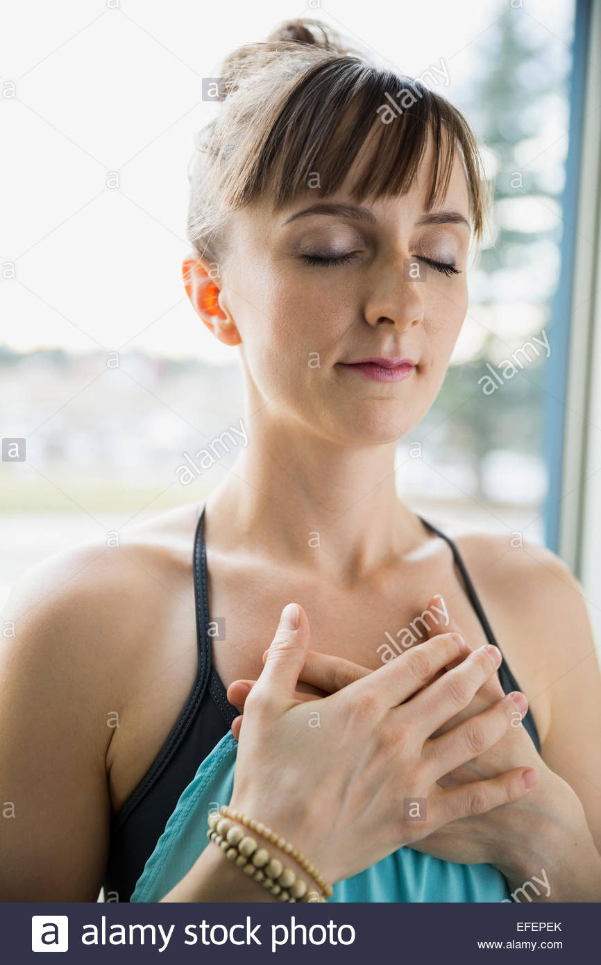 Woman meditating with hands over heart - Stock Image