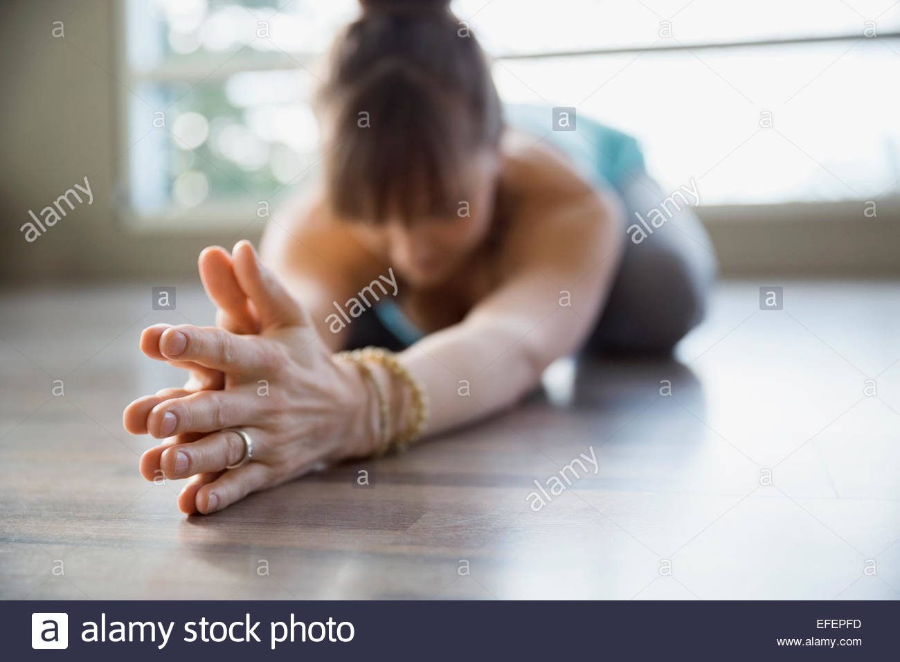 Woman in yoga childs pose with hands clasped - Stock Image
