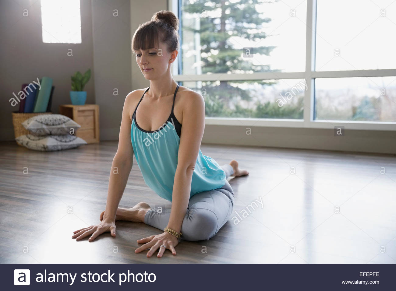 Woman practicing yoga in pigeon pose - Stock Image