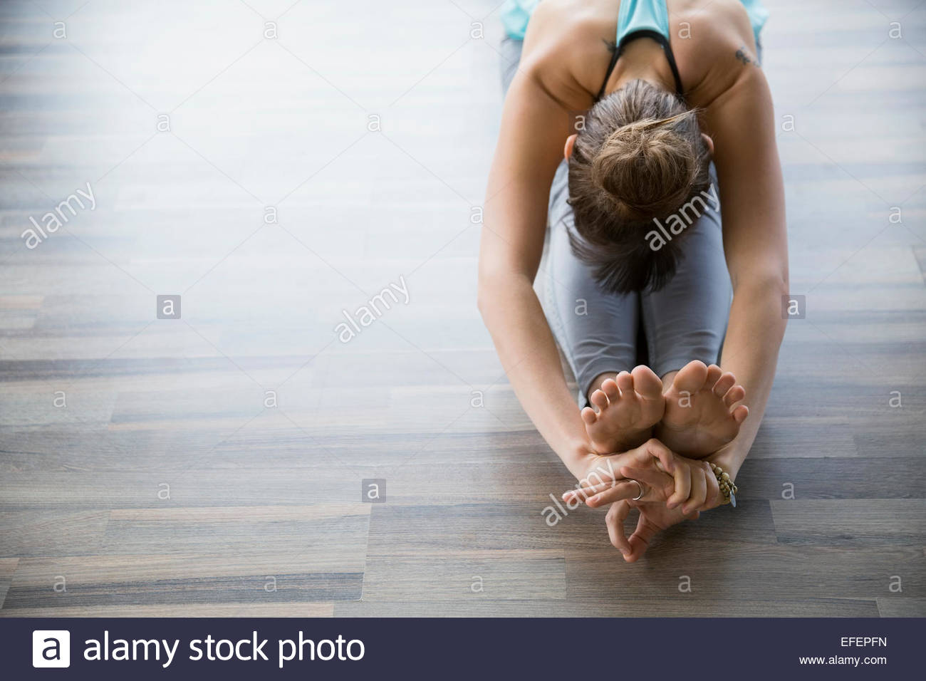 Woman in seated forward bend practicing mudra yoga - Stock Image
