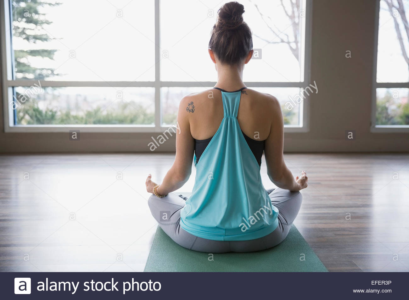 Rear view of woman meditating in lotus position - Stock Image