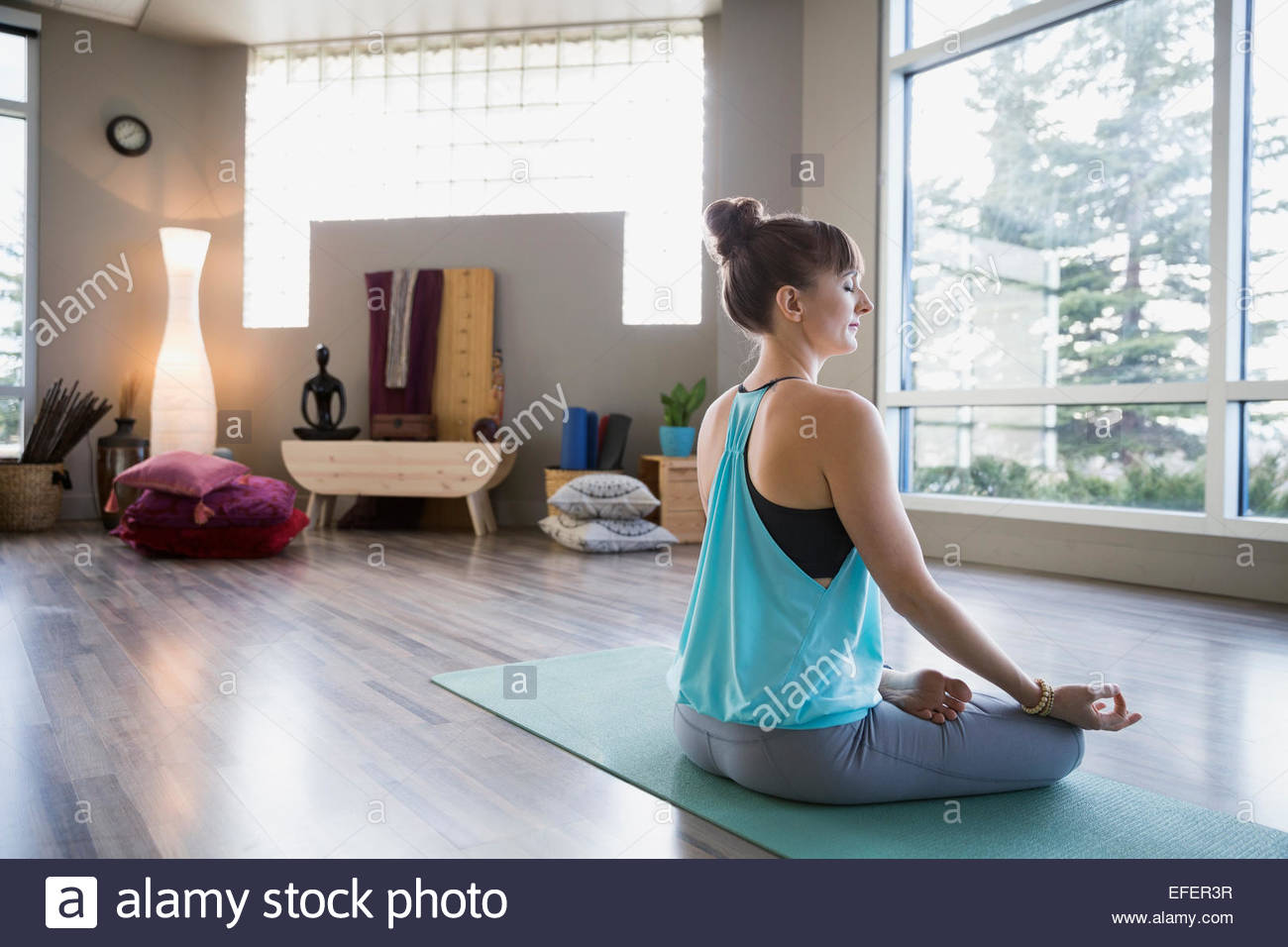 Woman meditating in mudra lotus position - Stock Image