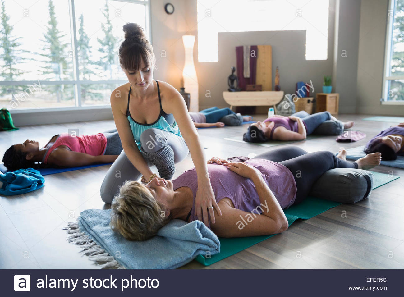 Instructor adjusting students shoulders in restorative yoga class - Stock Image