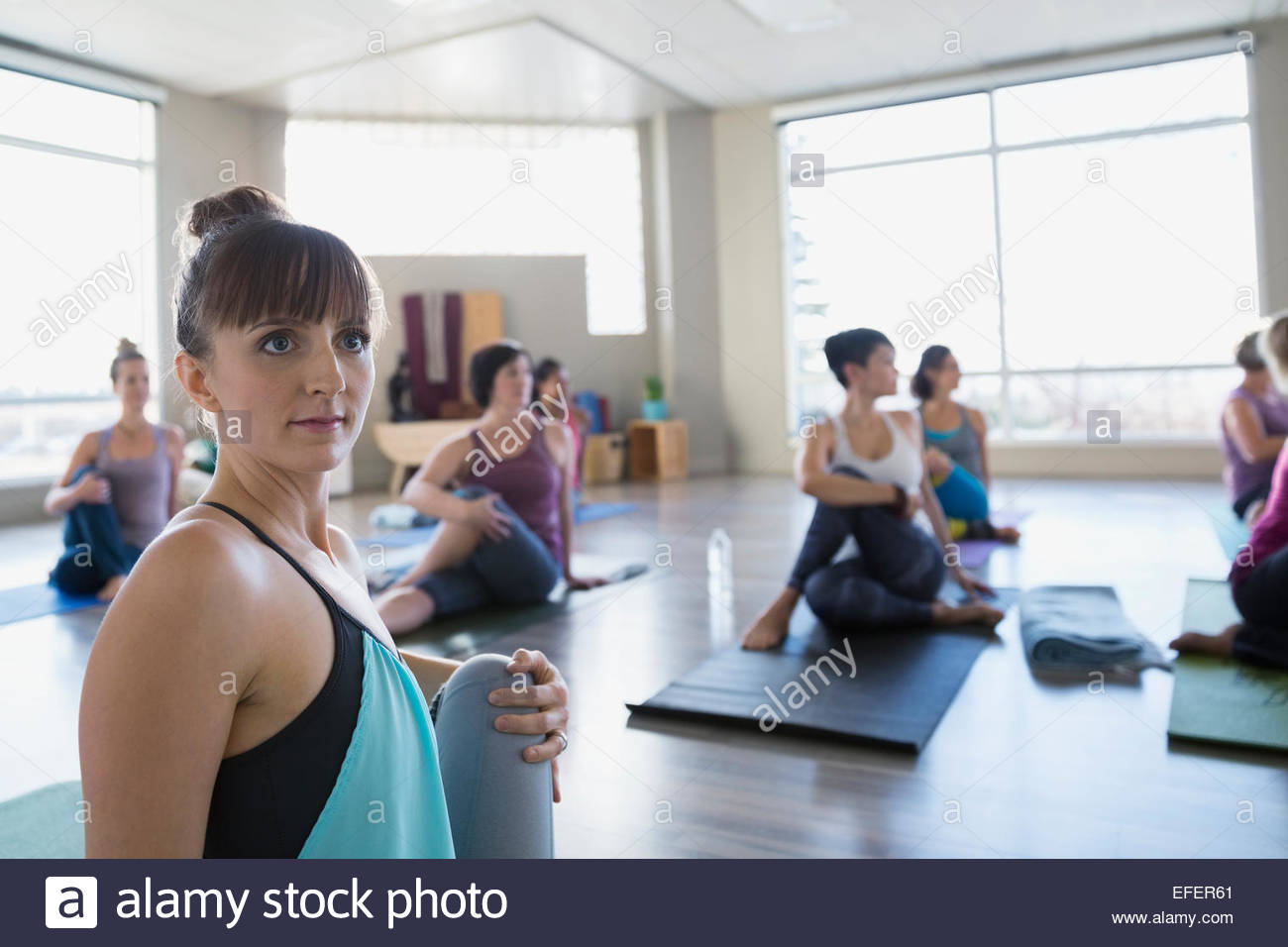 Women practicing seated twist pose in yoga class - Stock Image