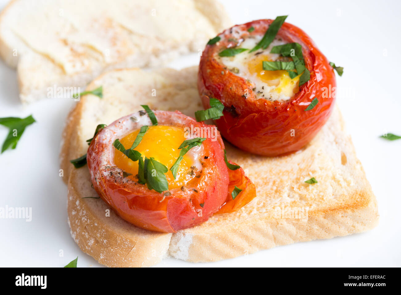 Baked, de-seeded tomatoes filled with an egg and finished in the oven, served on toast with a parsley garnish. This - Stock Image