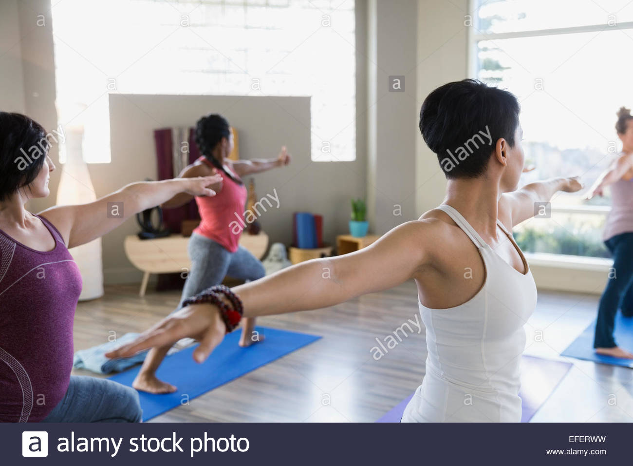 Women practicing warrior 2 pose in yoga class - Stock Image