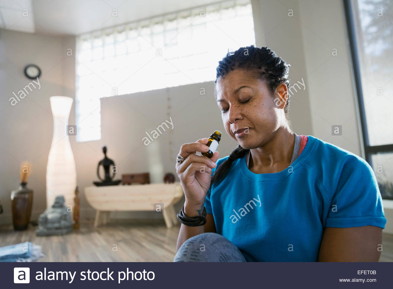 Woman smelling essential oil at yoga retreat - Stock Image