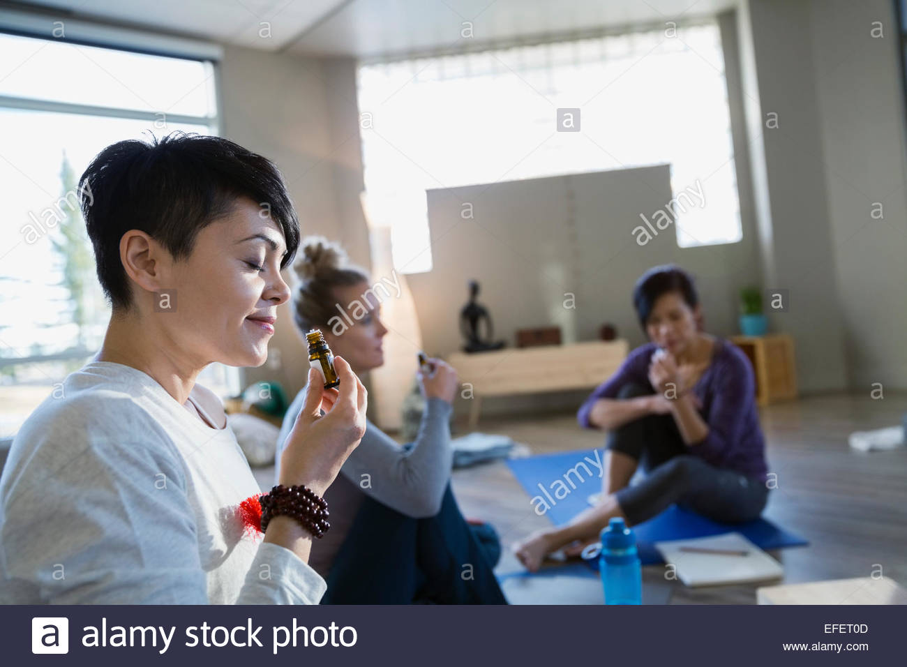 Women smelling essential oil at yoga retreat - Stock Image