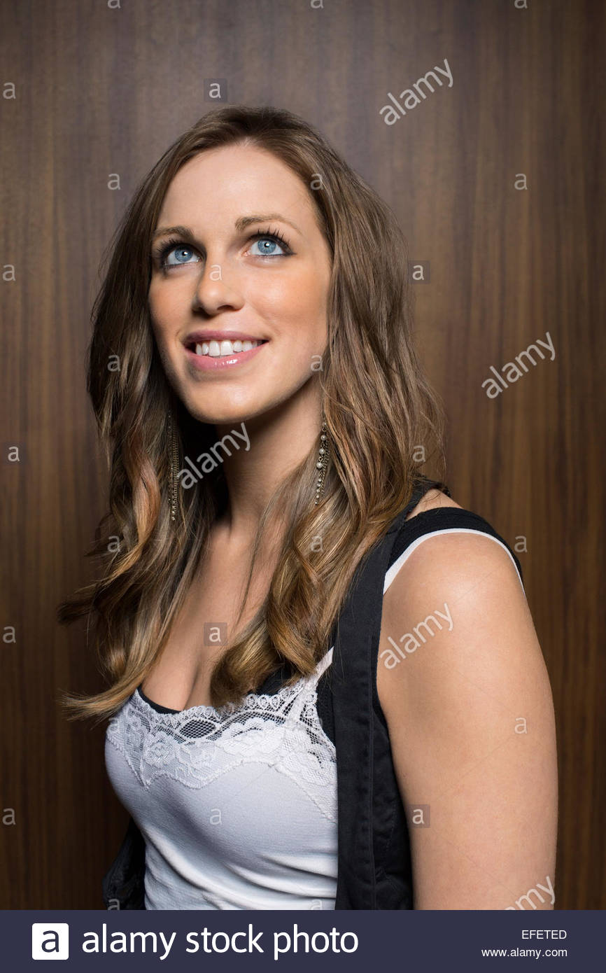 Smiling brunette woman looking up Stock Photo