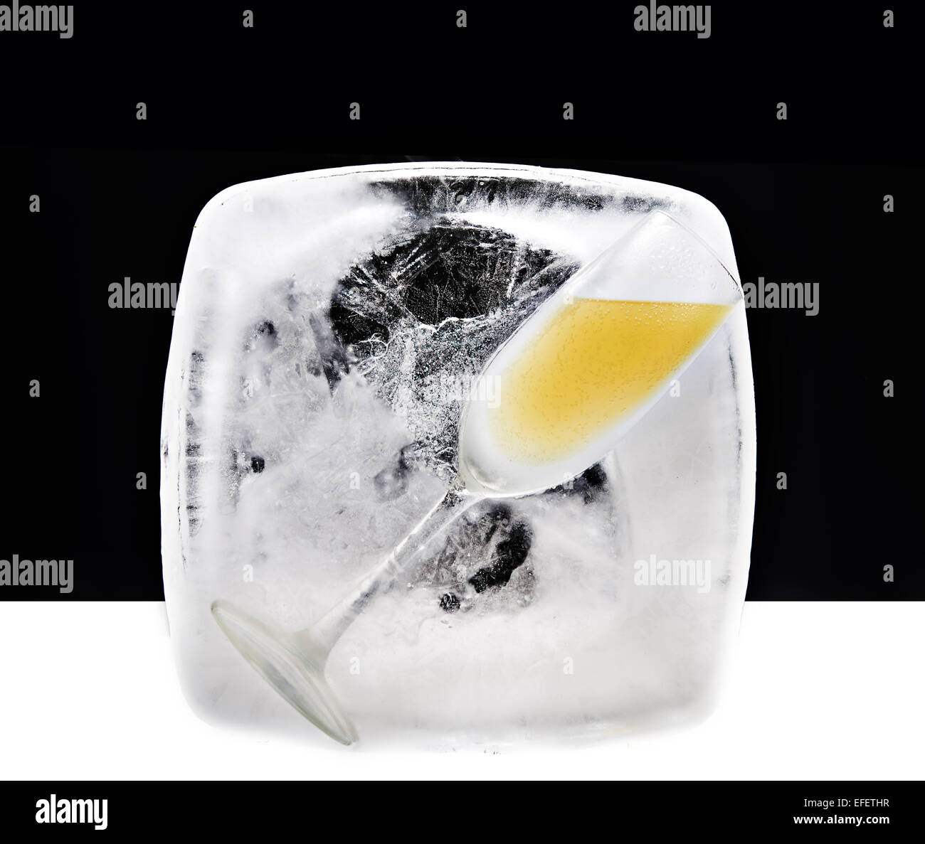 Champagne class filled with champagne in a block of ice - Stock Image
