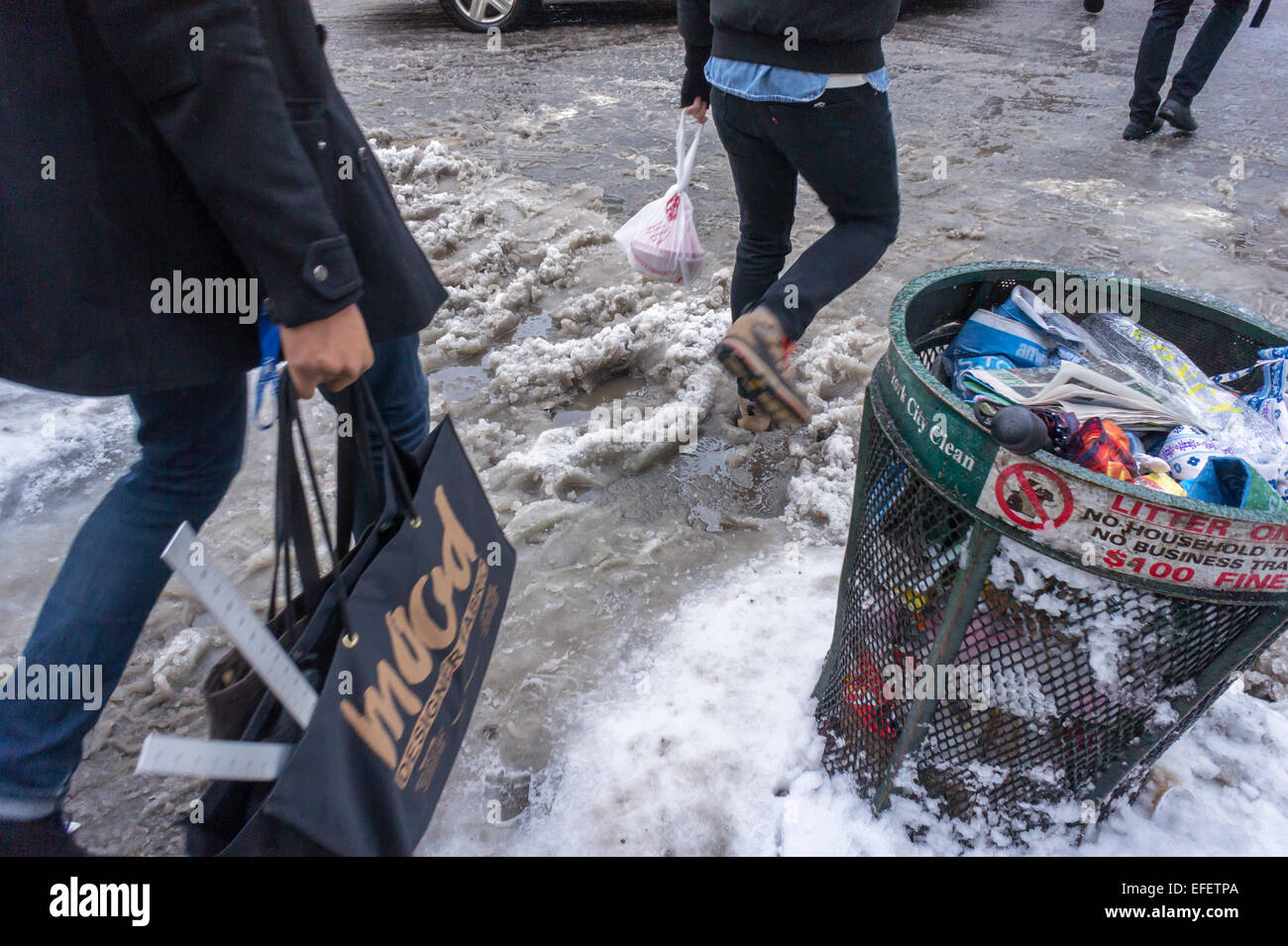 Pedestrians slog through puddles of slush and snow at street crossings with snow dam clogged storm drains in the - Stock Image
