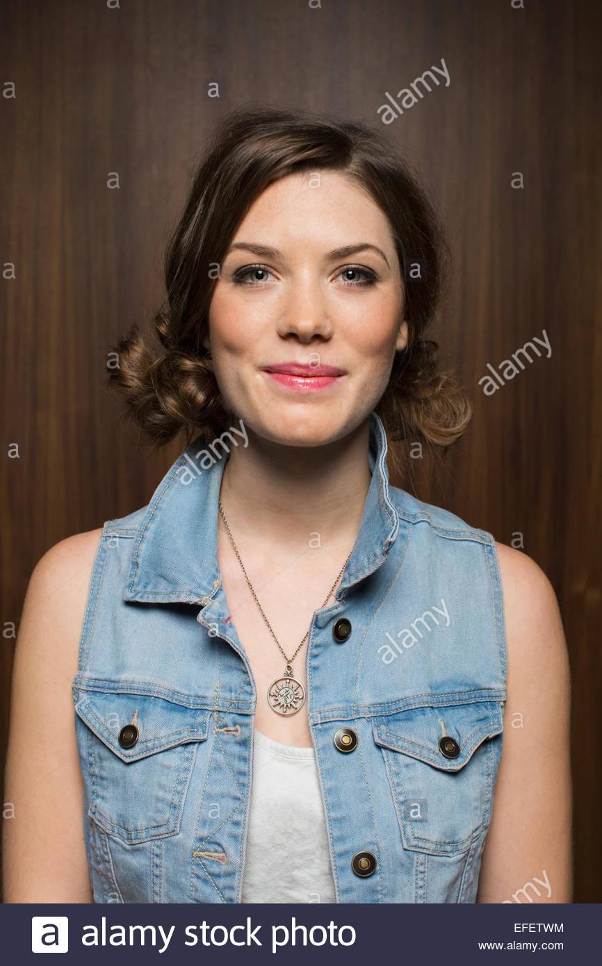 Portrait of smiling woman wearing sleeveless denim jacket - Stock Image