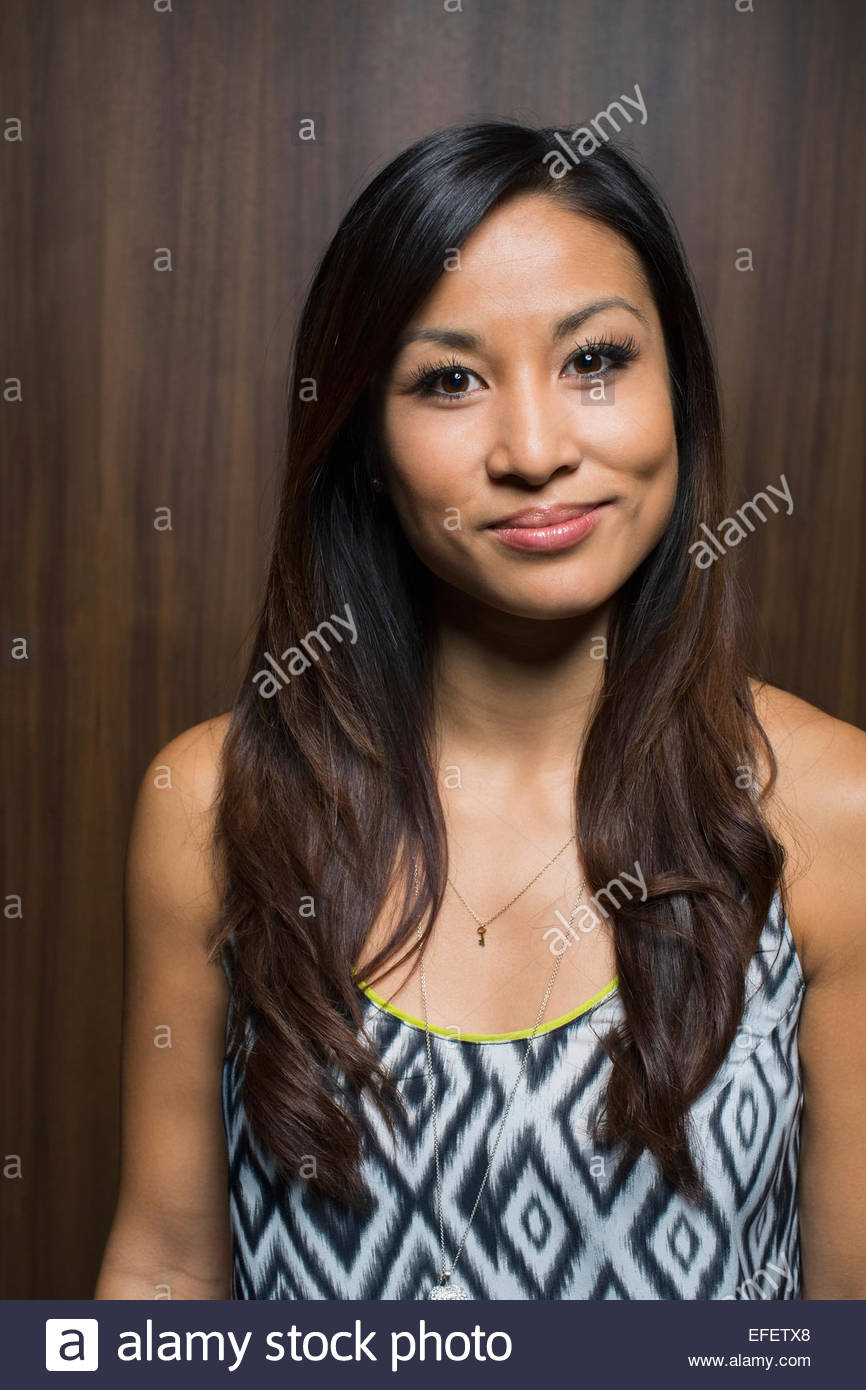 Portrait of smiling brunette wearing patterned sleeveless top - Stock Image