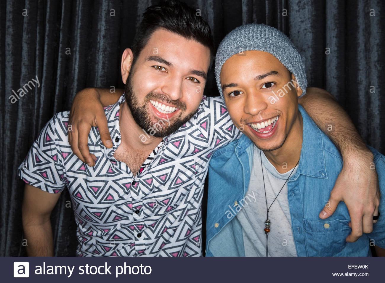 Portrait of smiling men hugging - Stock Image