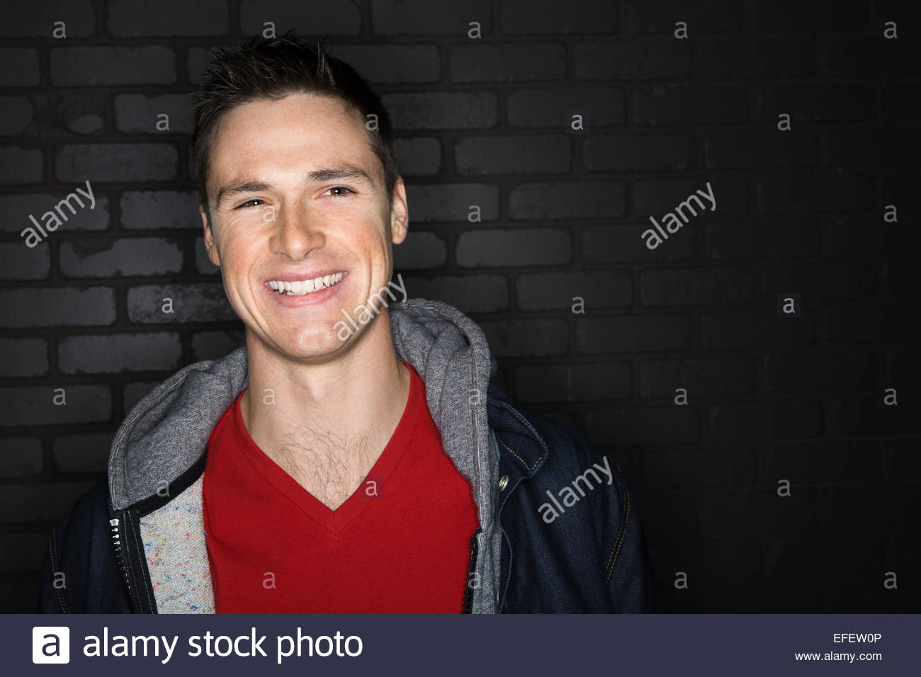 Portrait of smiling brunette man wearing jacket - Stock Image
