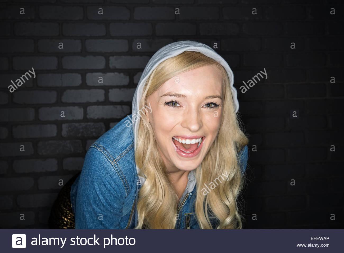 Portrait of laughing blonde woman wearing hoody - Stock Image