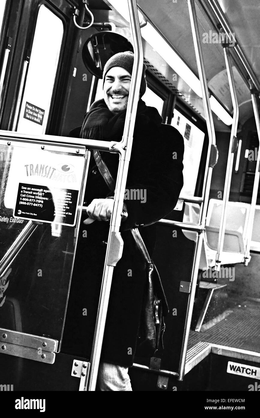 Man on bus laughing while standing up in BW - Stock Image