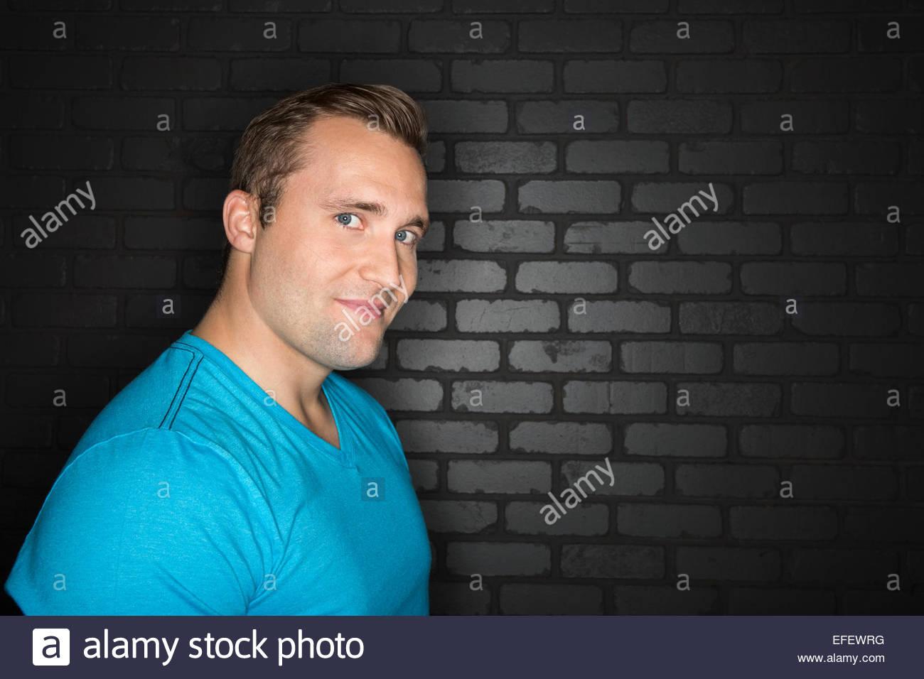 Portrait of confident man in blue t-shirt - Stock Image