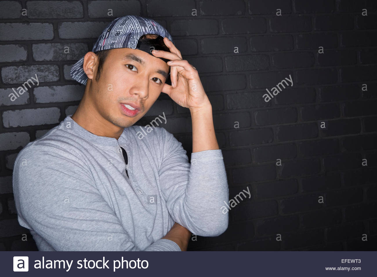 Portrait of serious man with backward baseball cap - Stock Image