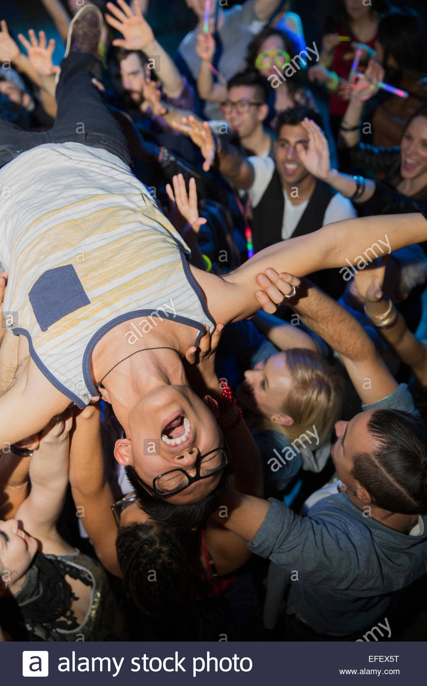 Enthusiastic man crowdsurfing at concert - Stock Image