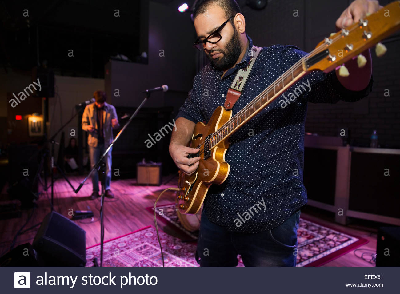 Musical performer tuning guitar on stage - Stock Image