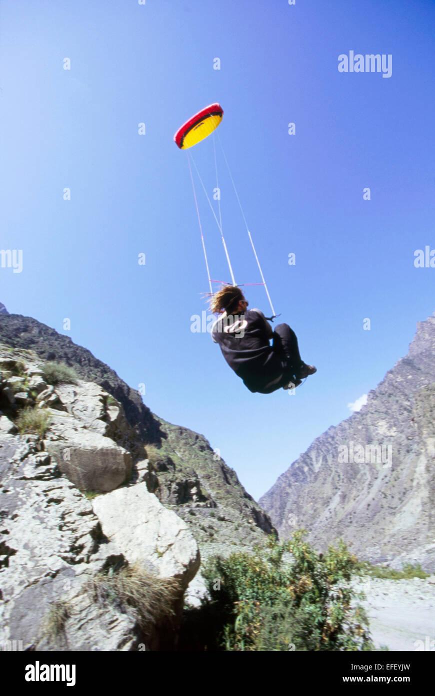 Power kite flier taking air in Karakoram range Pakistan - Stock Image