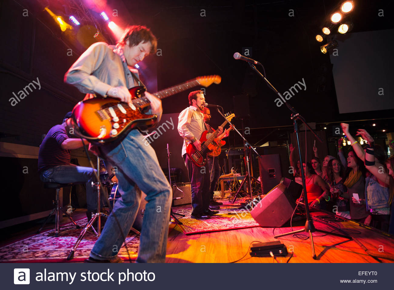 Musicians performing on stage at concert - Stock Image