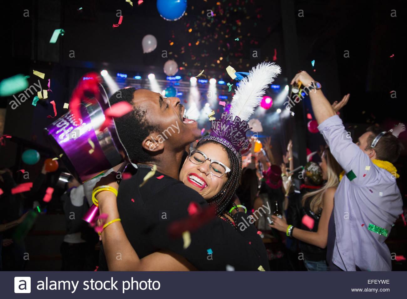 Confetti falling hugging couple enjoying New Year celebration - Stock Image