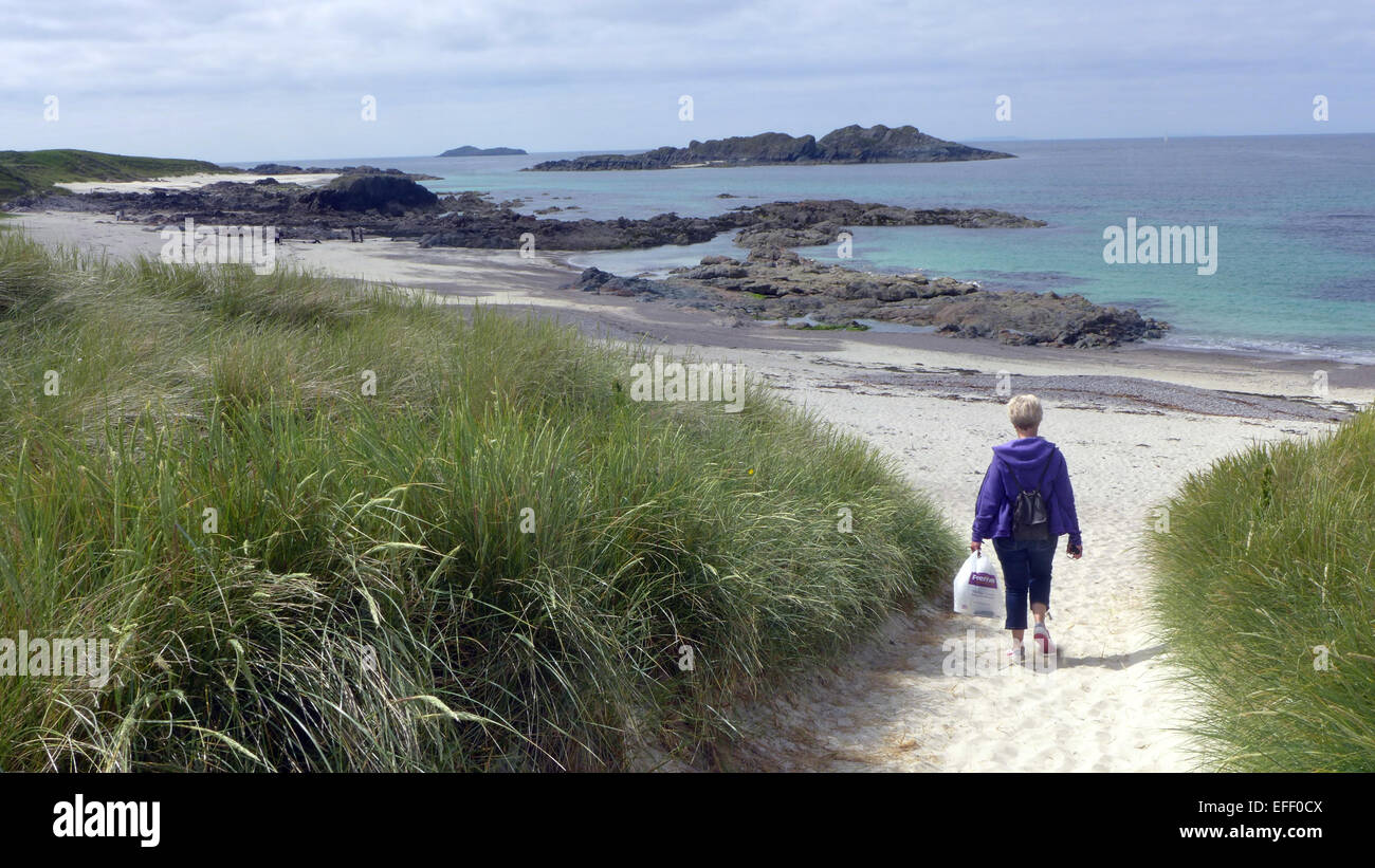 A holiday maker walking onto Traigh an t-Suidhe on Iona Scotland Stock Photo
