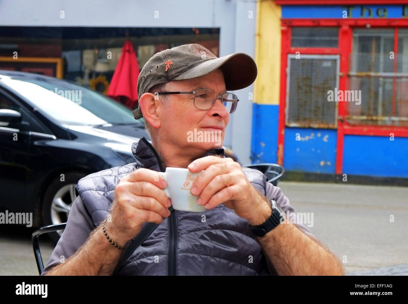 Middle aged man enjoys a coffee in an outdoor cafe wine bar in west Cork Ireland - Stock Image