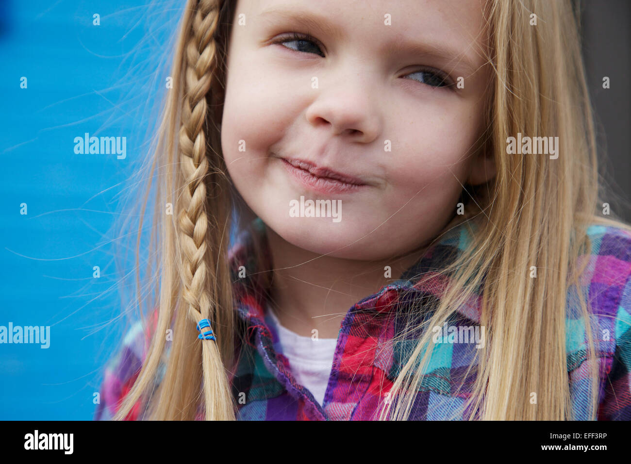 Young blonge girl with braid smirking. - Stock Image