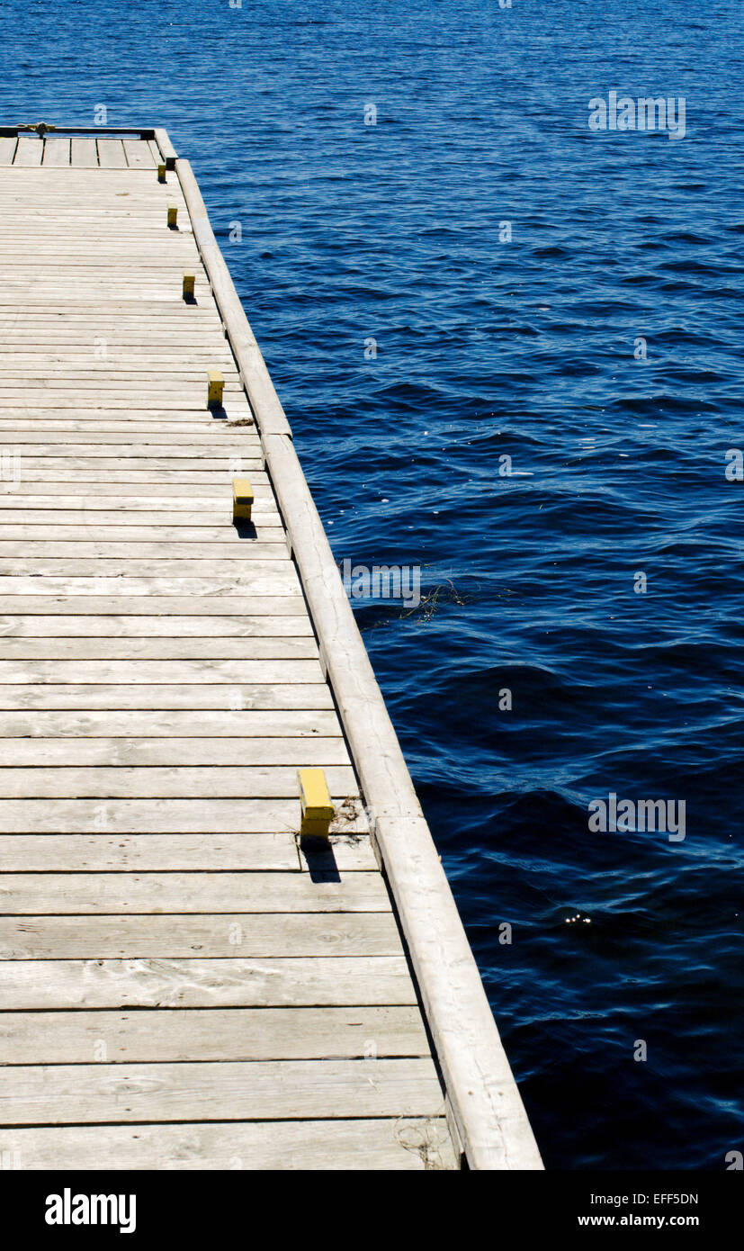 Part of gray wooden dock with metal cleats on blue water. - Stock Image