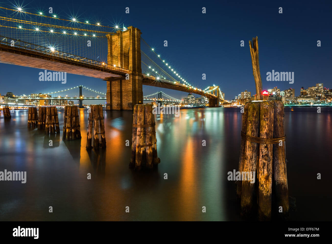 Illuminated Brooklyn Bridge by night as viewed from the Manhattan side. - Stock Image