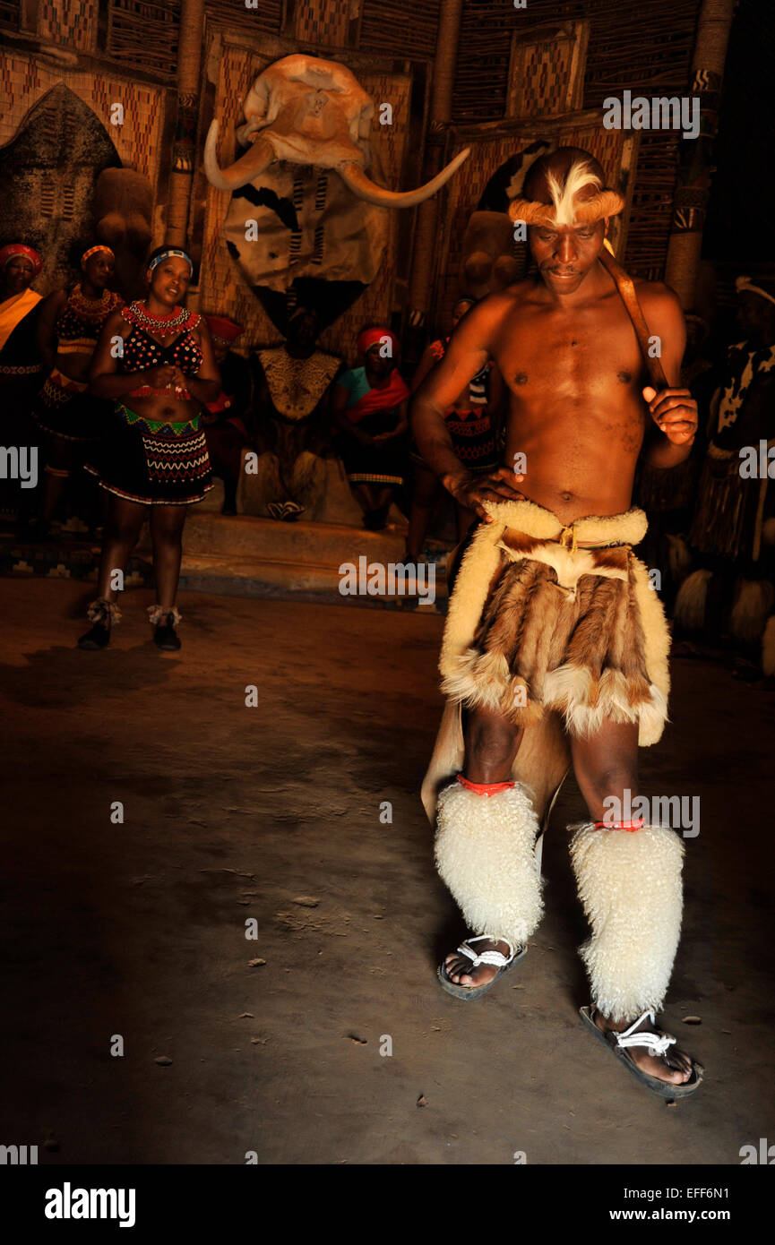 Muscular adult male dancer in traditional Zulu culture dress performing a solo love dance with troupe of performers - Stock Image