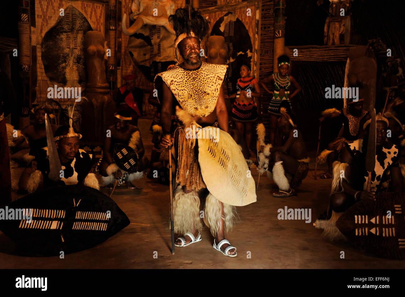 Adult man in traditional dress, Zulu chief with shield, dancers in warrior dress, traditional dance show, Shakaland, KwaZulu-Natal, South Africa Stock Photo