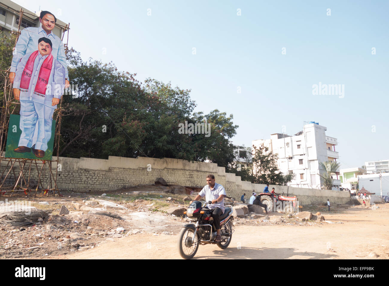 An Indian rides past a huge hoarding of Telangana Chief Minister K Chandra Sekhar popularly known as KCR in Hyderabad,Indian - Stock Image