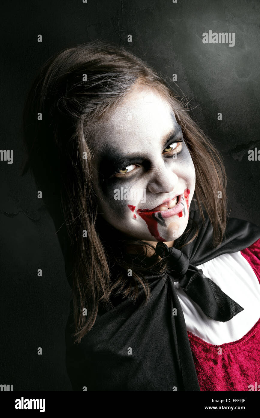 Girl with face-paint and Halloween vampire costume in a dark Stock ...