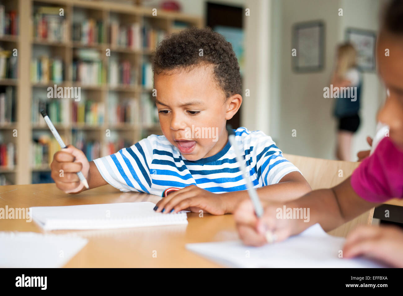 Cute boy writing in book by classmate at classroom - Stock Image