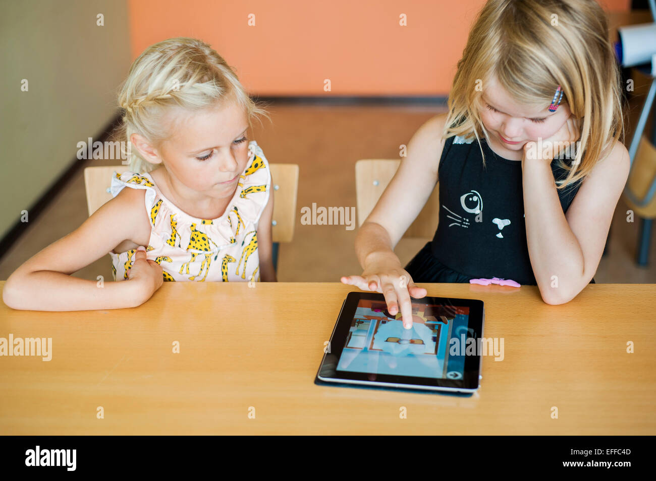 Girl watching classmate drawing on digital tablet in classroom - Stock Image