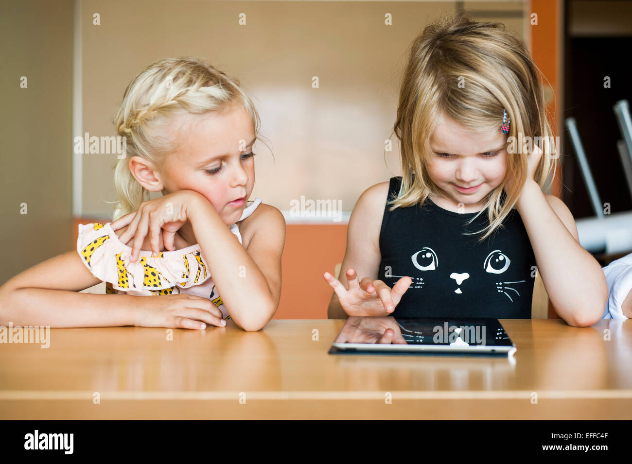 Girl watching classmate using digital tablet in classroom - Stock Image