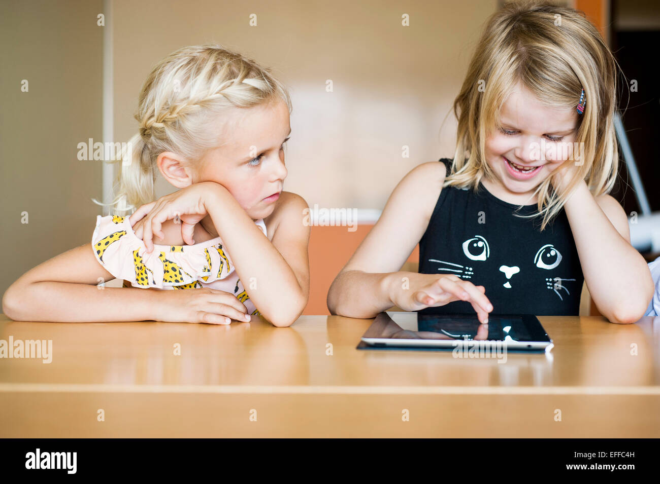 Girl watching classmate using tablet computer in classroom - Stock Image